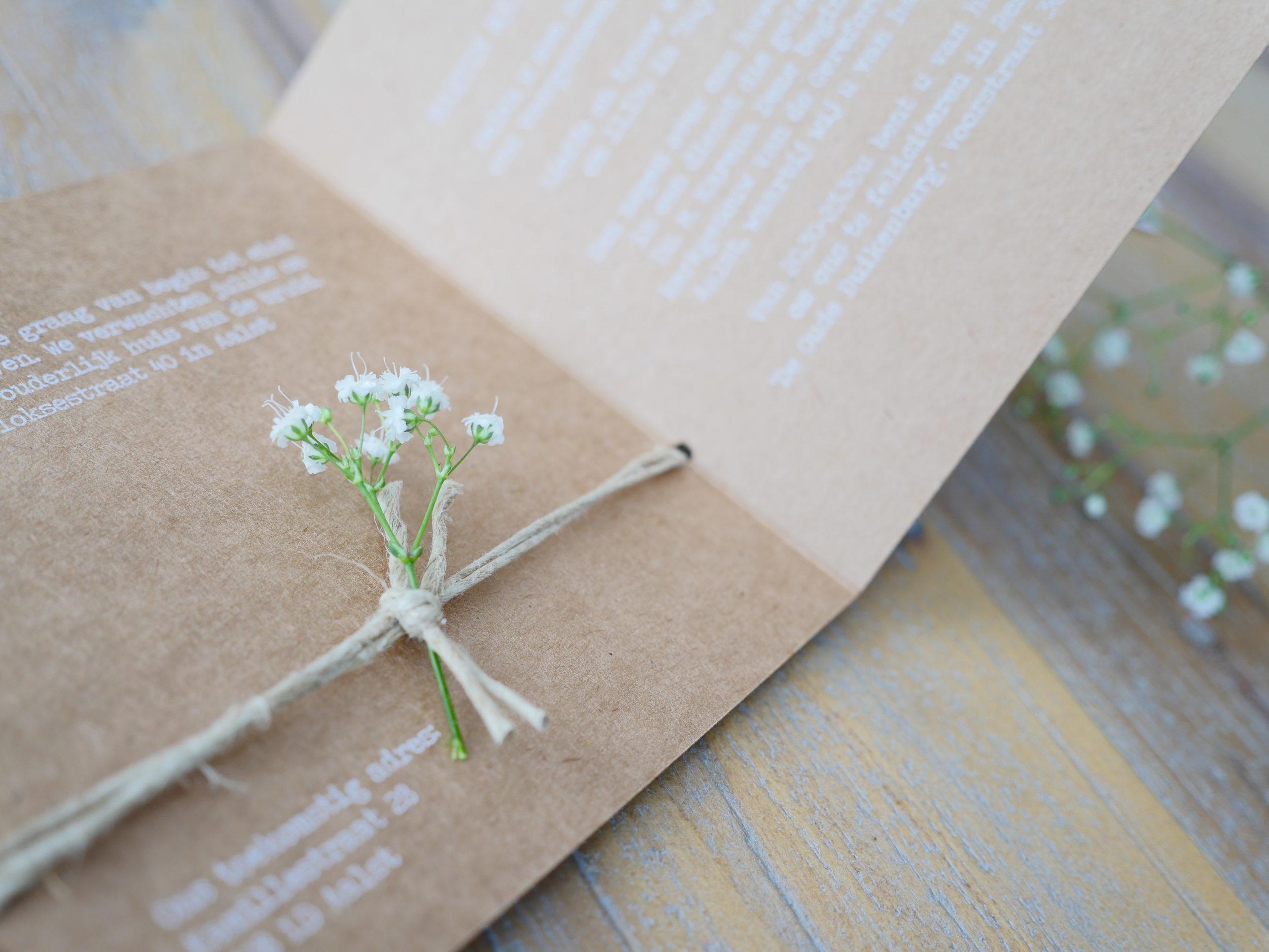 Deze romantische trouwkaart heeft een rustieke en natuurlijke uitstraling dankzij het label dat met touw vastgeknoopt wordt aan de kaart.Stijlvol door het gebruik van witte inkt op echt kraftkarton.Het touw, takje gipskruid en de bijpassende sluitsticker maken het helemaal af.